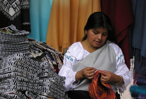 Women knitting a red hat in a market in Ecuador