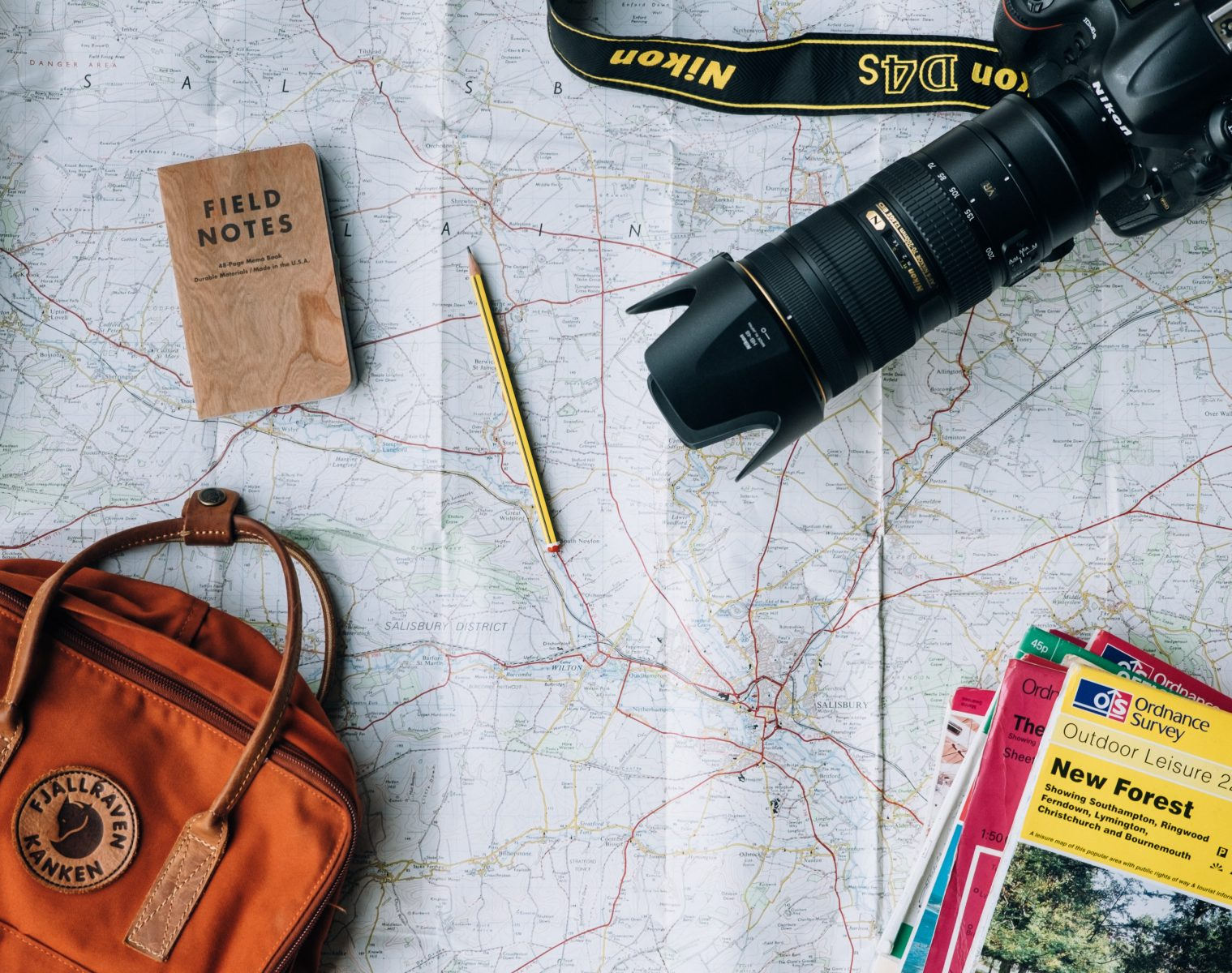 Camera, notebooks, rucksack and pen on a road map