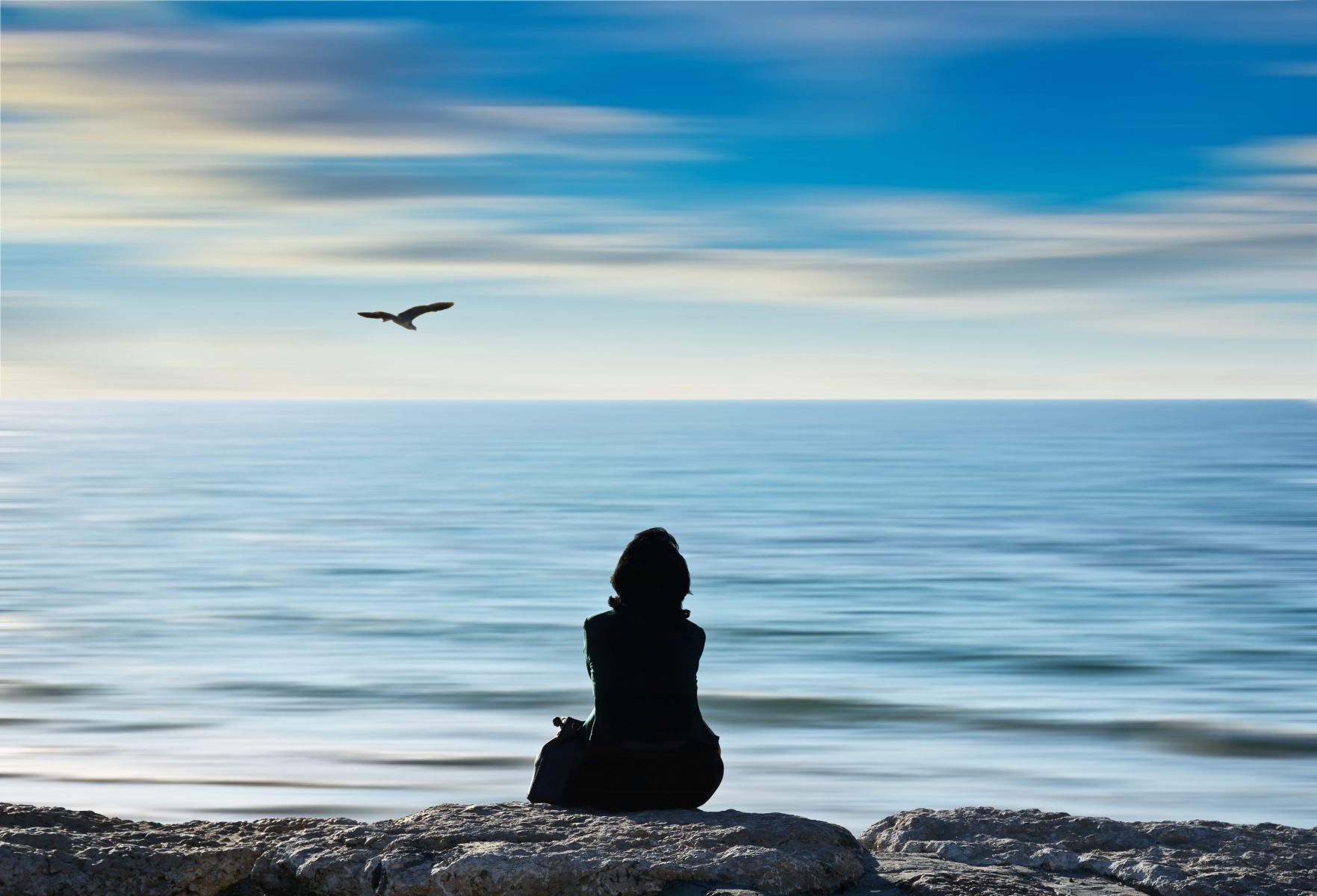 Woman sitting on a rock facing the sea