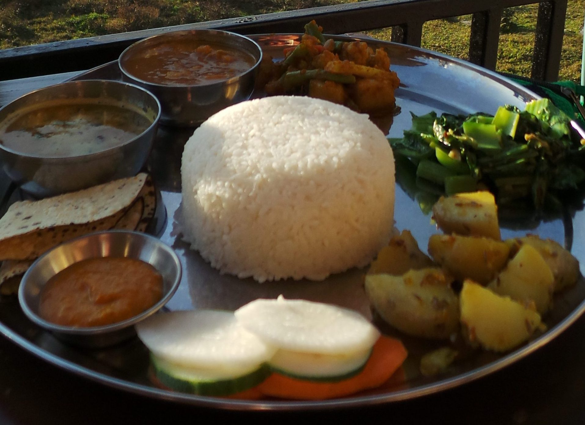 Rice served with vegetables and curries on a silver plate