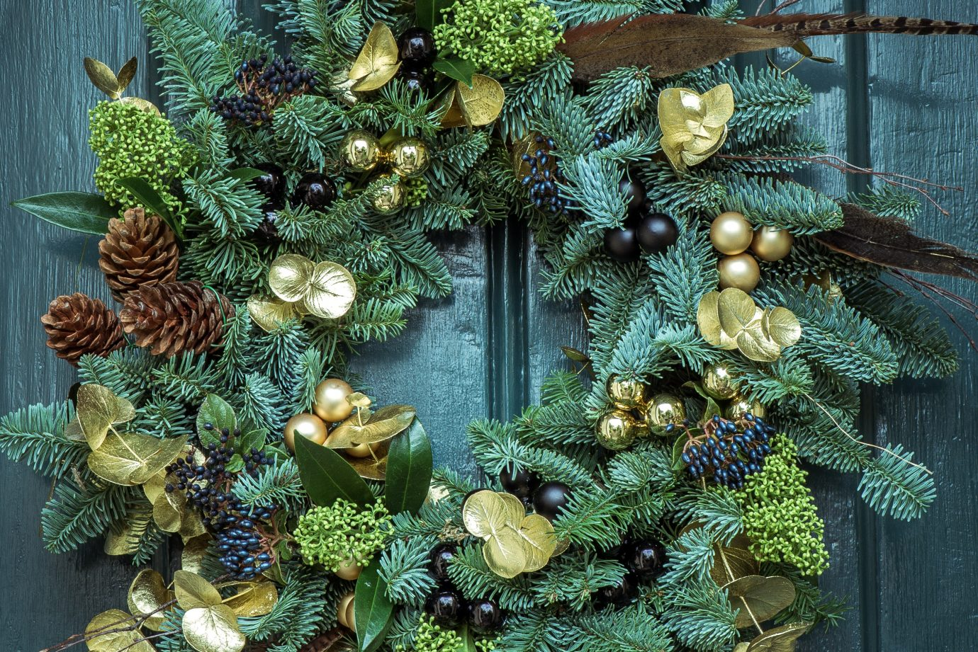 Green and golden Christmas wreath on a green door