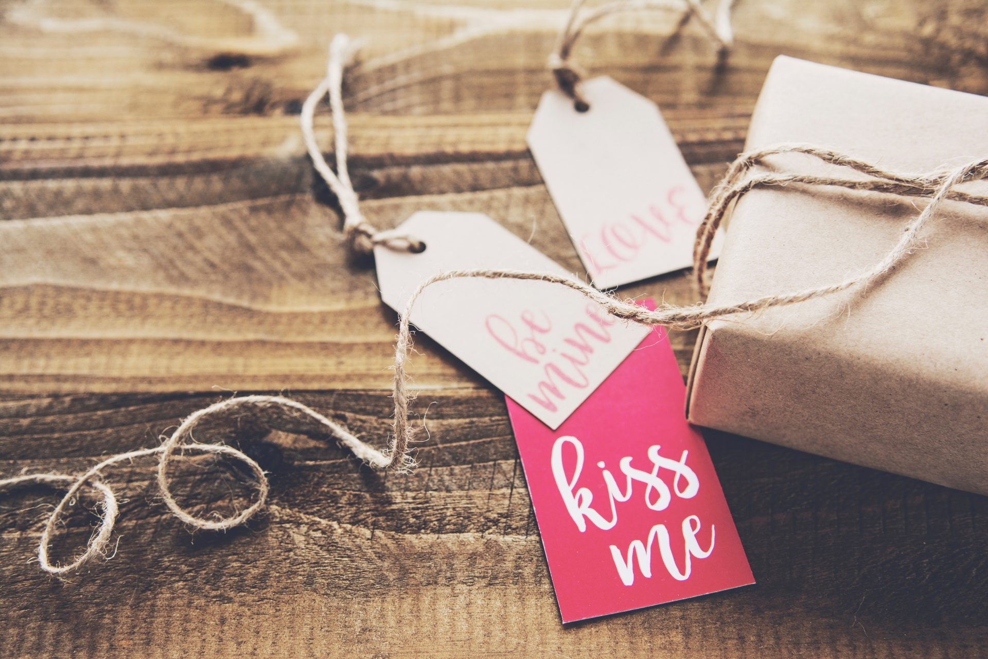 Gift with kiss me, love and be mine tags on a table
