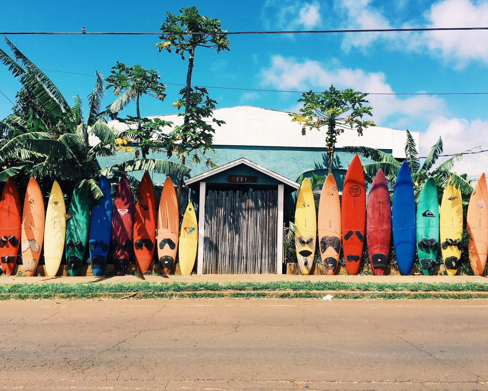 Colourful surfboards displayed on the side of the road