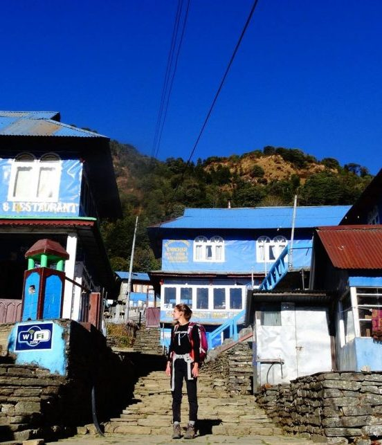 Woman standing in a village of blue houses