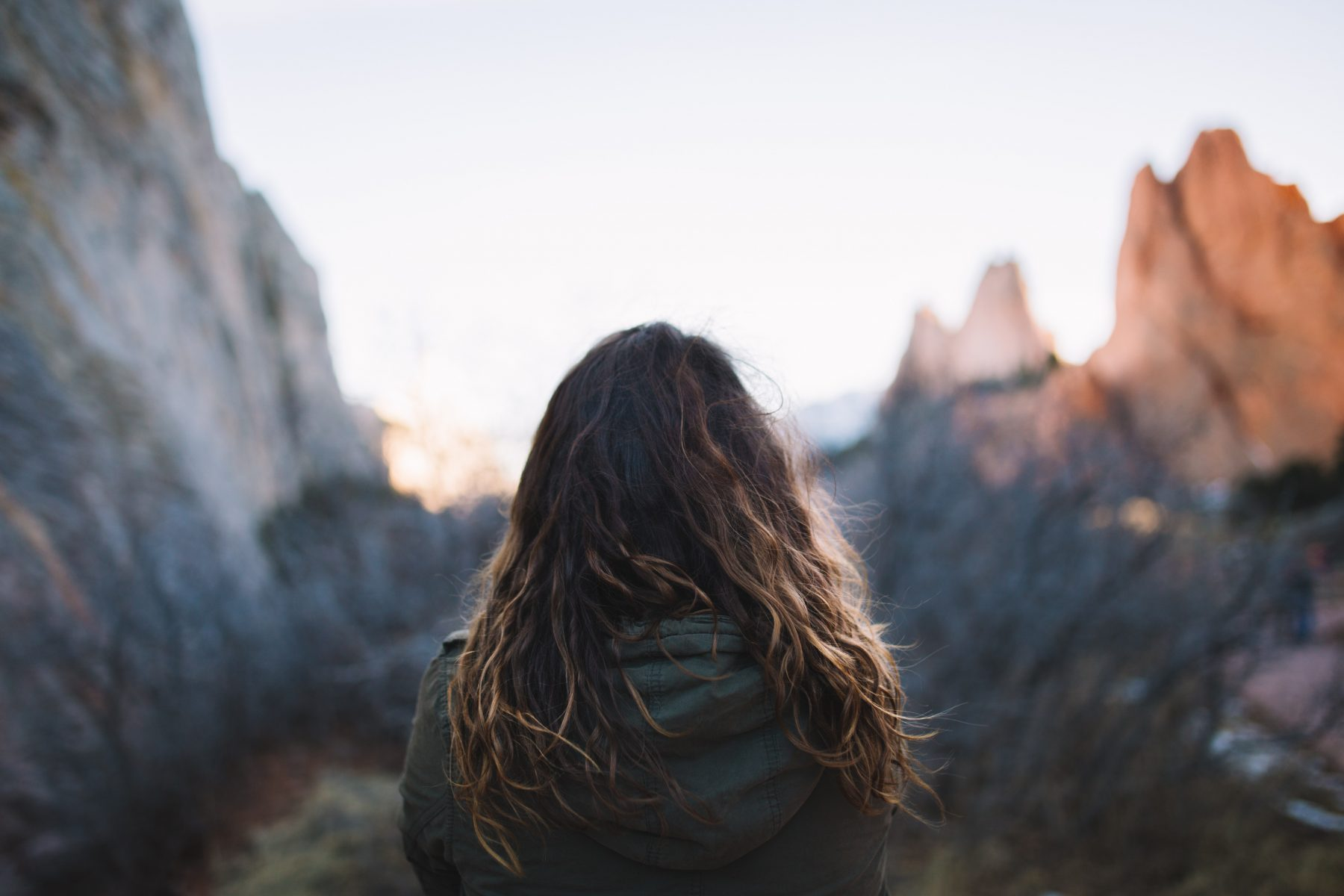 Woman looking at the sunset over rocky peaks in Colorado