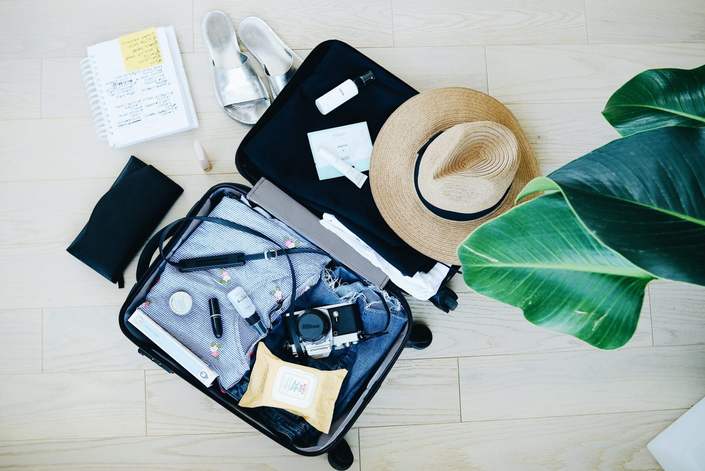 Open suitcase with travel accessories and clothes