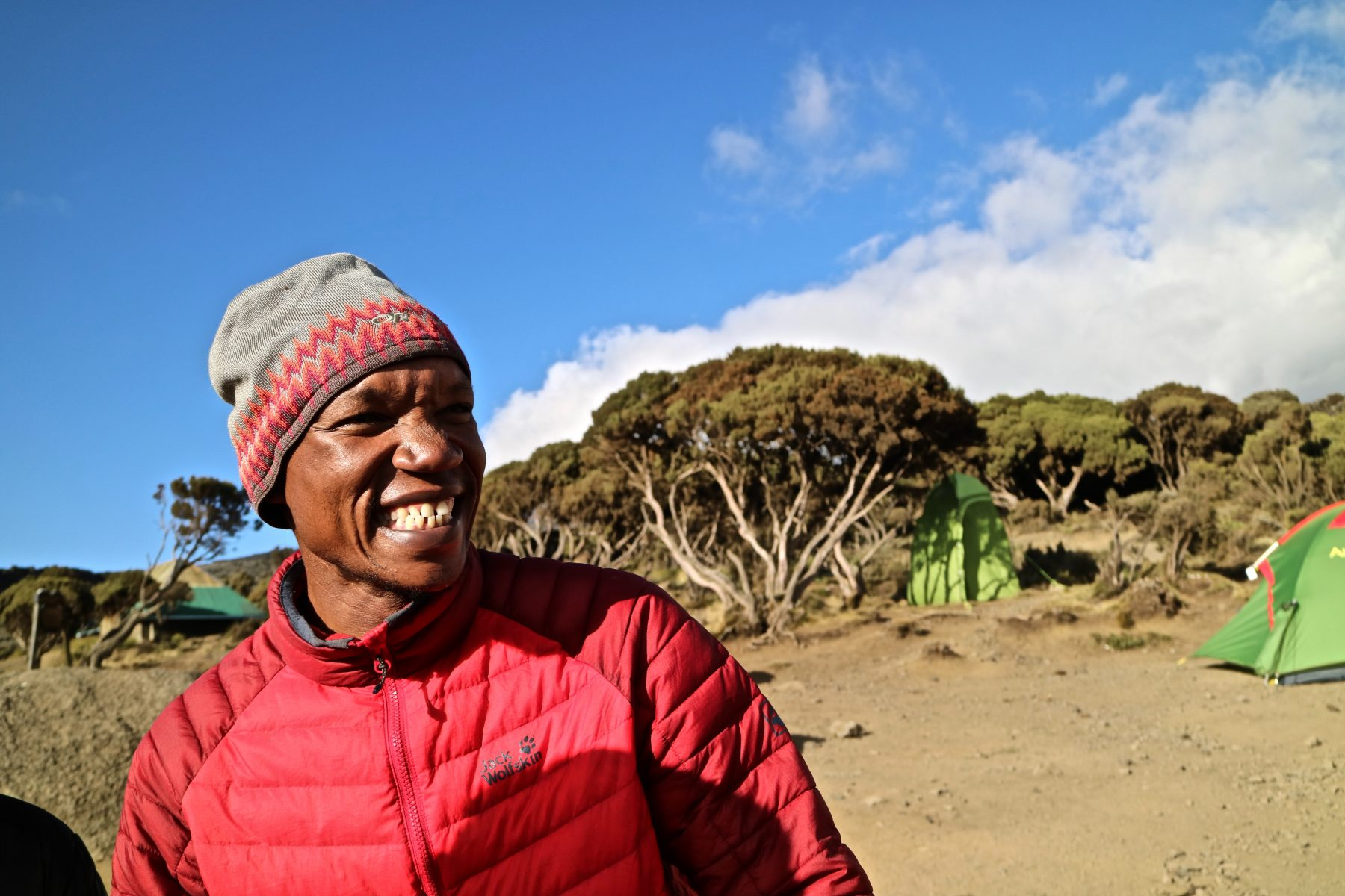 Local Kilimanjaro guide smiling and wearing a red jacket