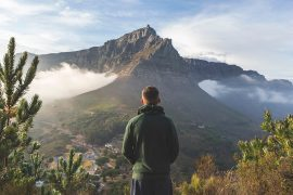 Man looking at the view of Cape Town lying at the bottom of a mountain