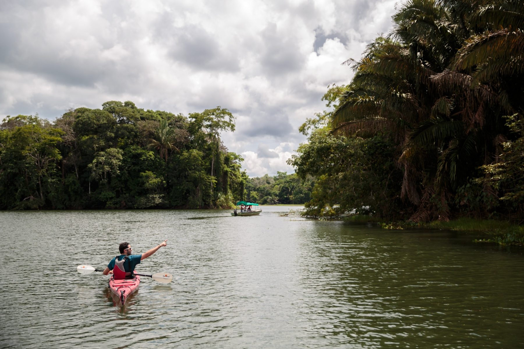 Man kayaking on a canal and pointing to the jungle.