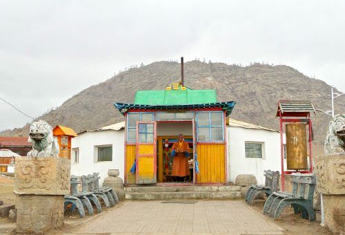 Monk coming out of a colourful temple in Mongolia