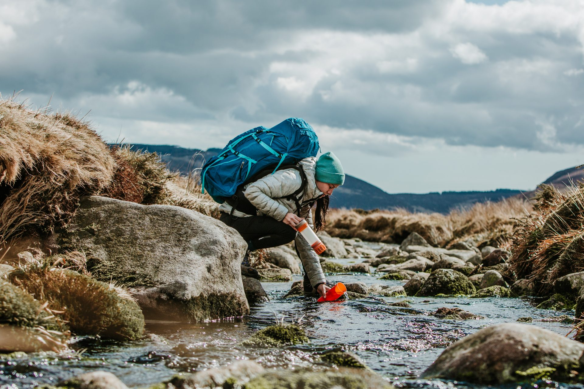 Woman in outdoor gear filling her water bottle in a river
