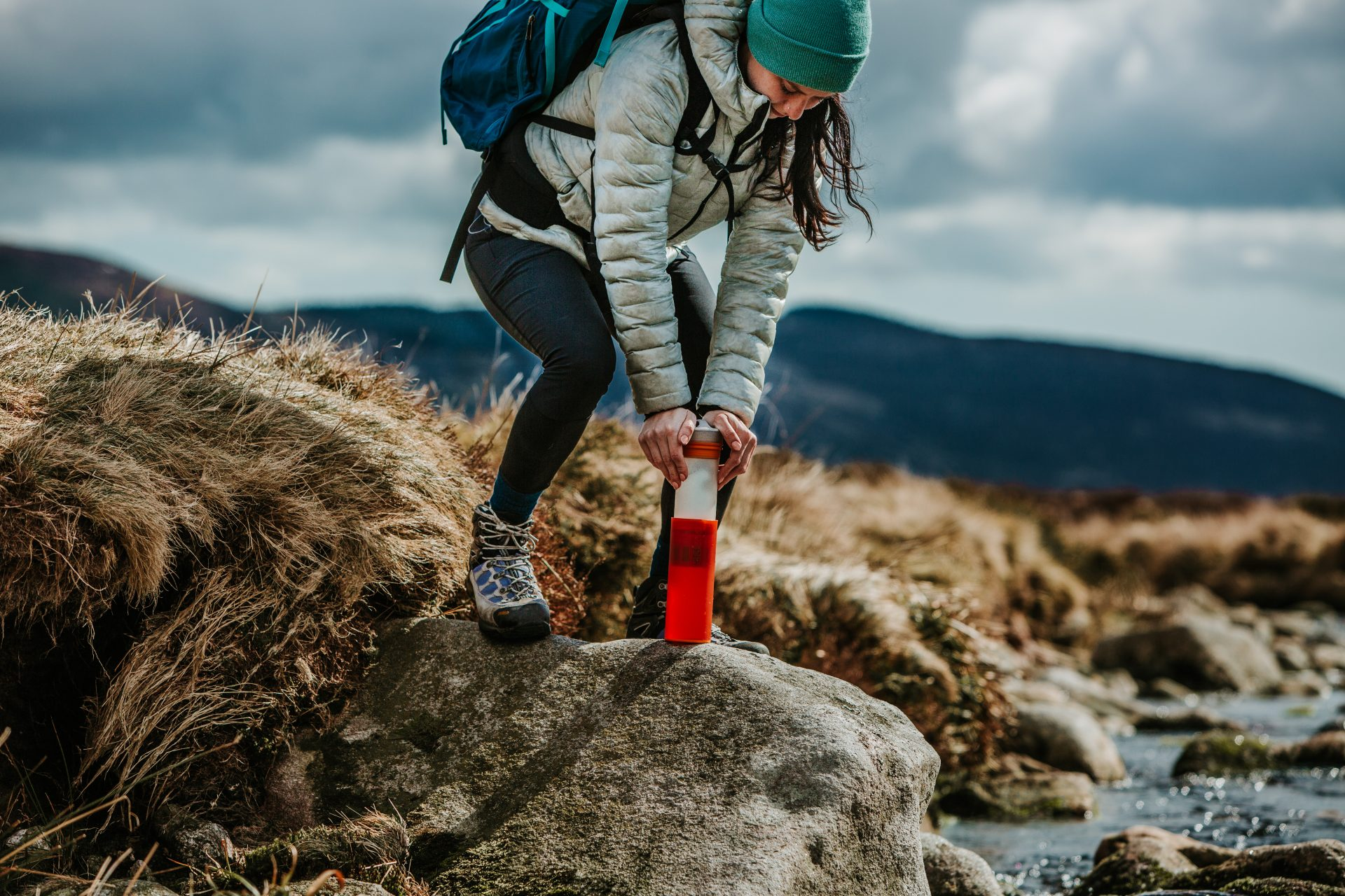 Woman in outdoor gear pressing down on a water bottle to filter the water