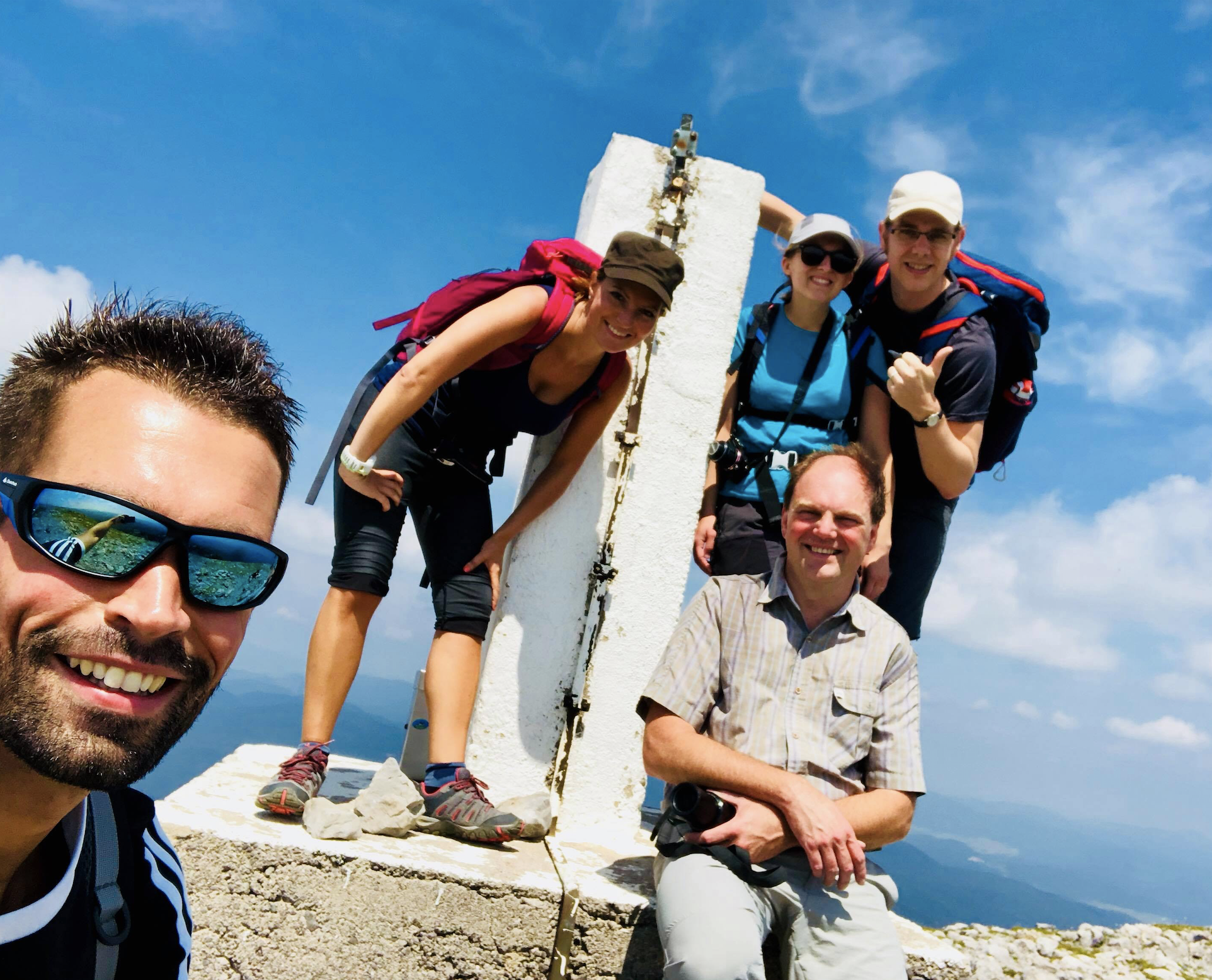 Group of five people taking a selfie at the top of a mountain