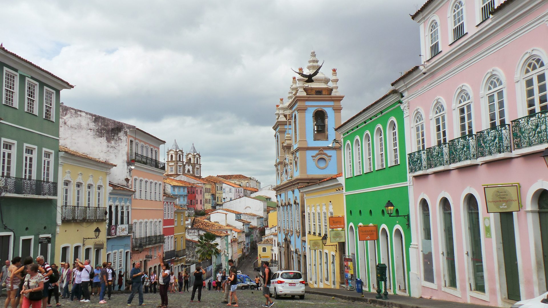 People standing in a street full of colourful colonial buildings