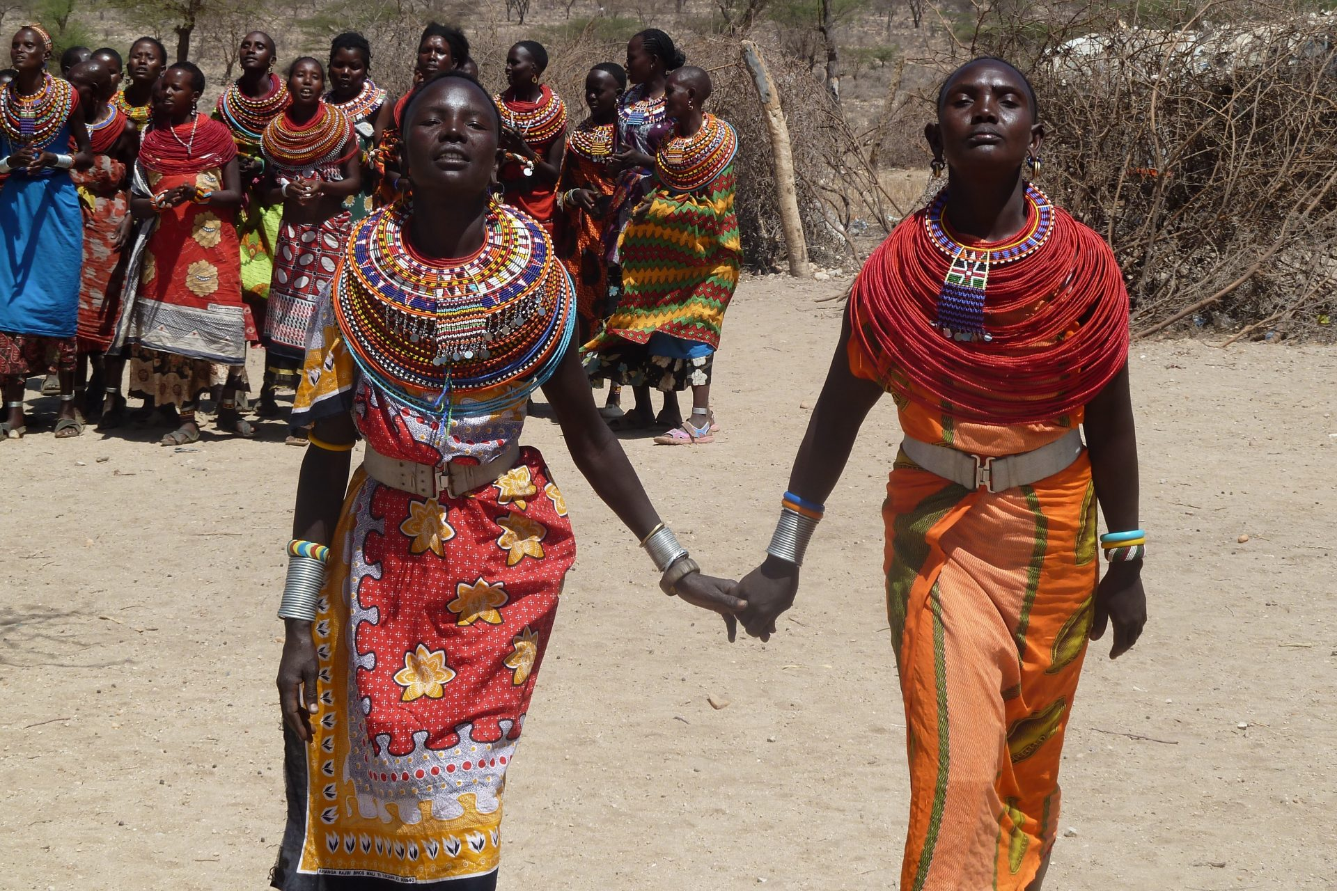 Two kenyan women dressed in colourful clothes holding hands