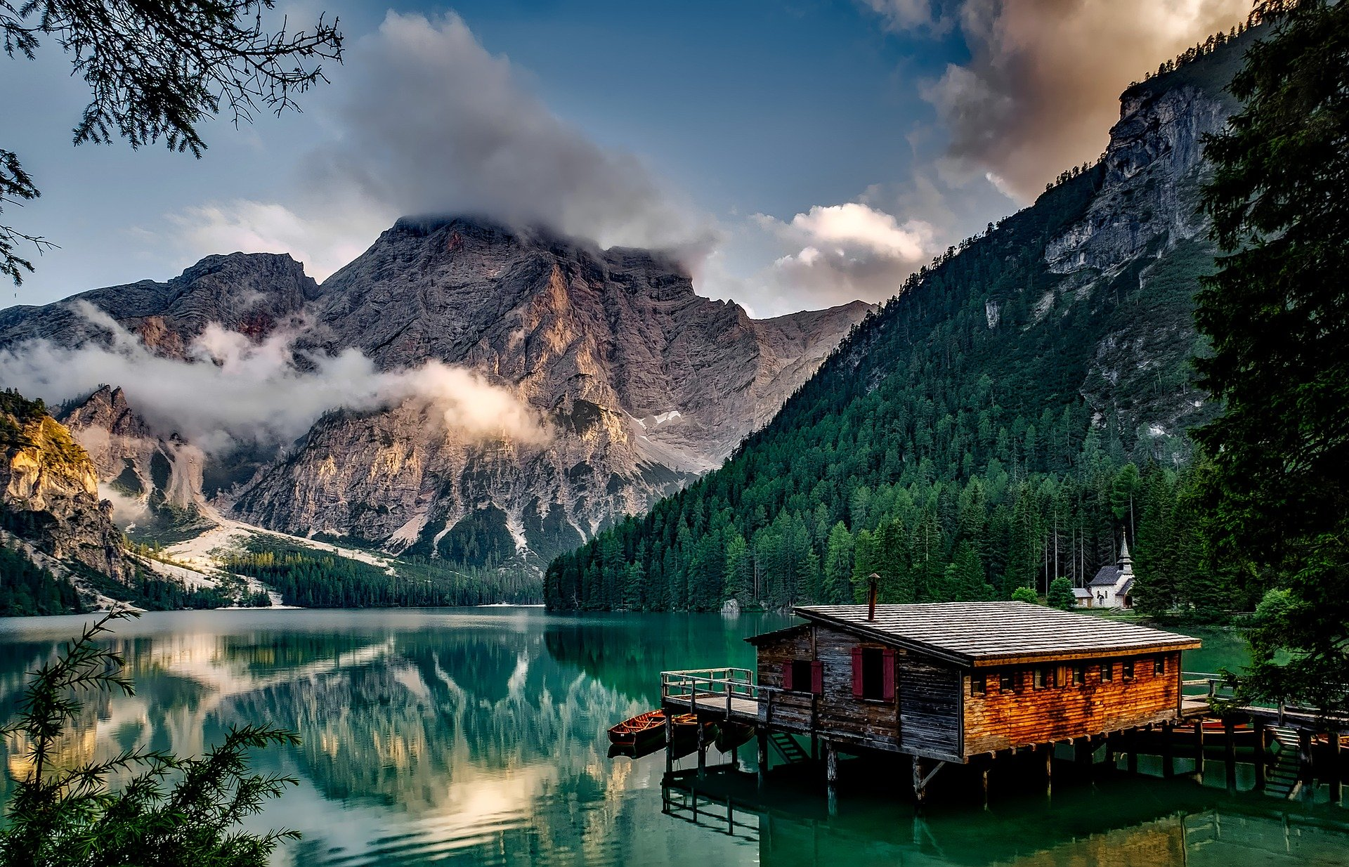 Wooden house on a lake surrounded by mountains
