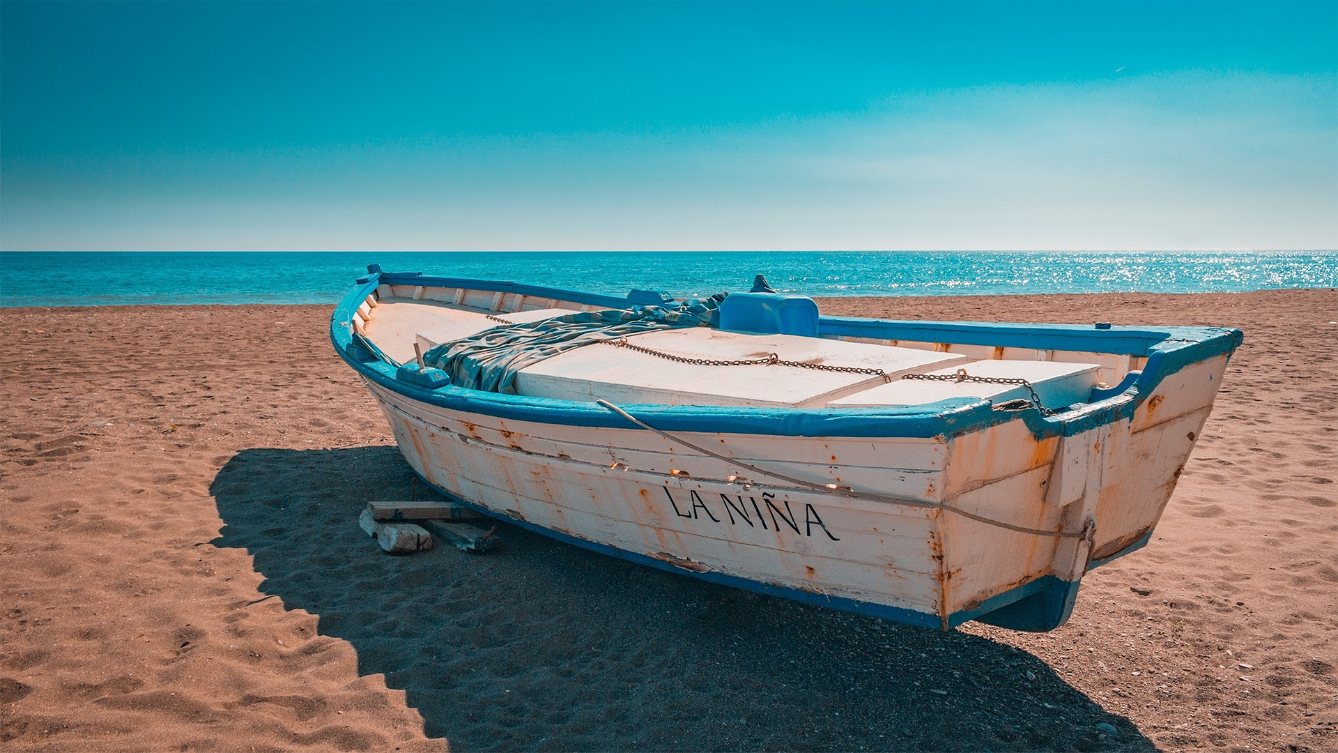 White and blue boat on the beach