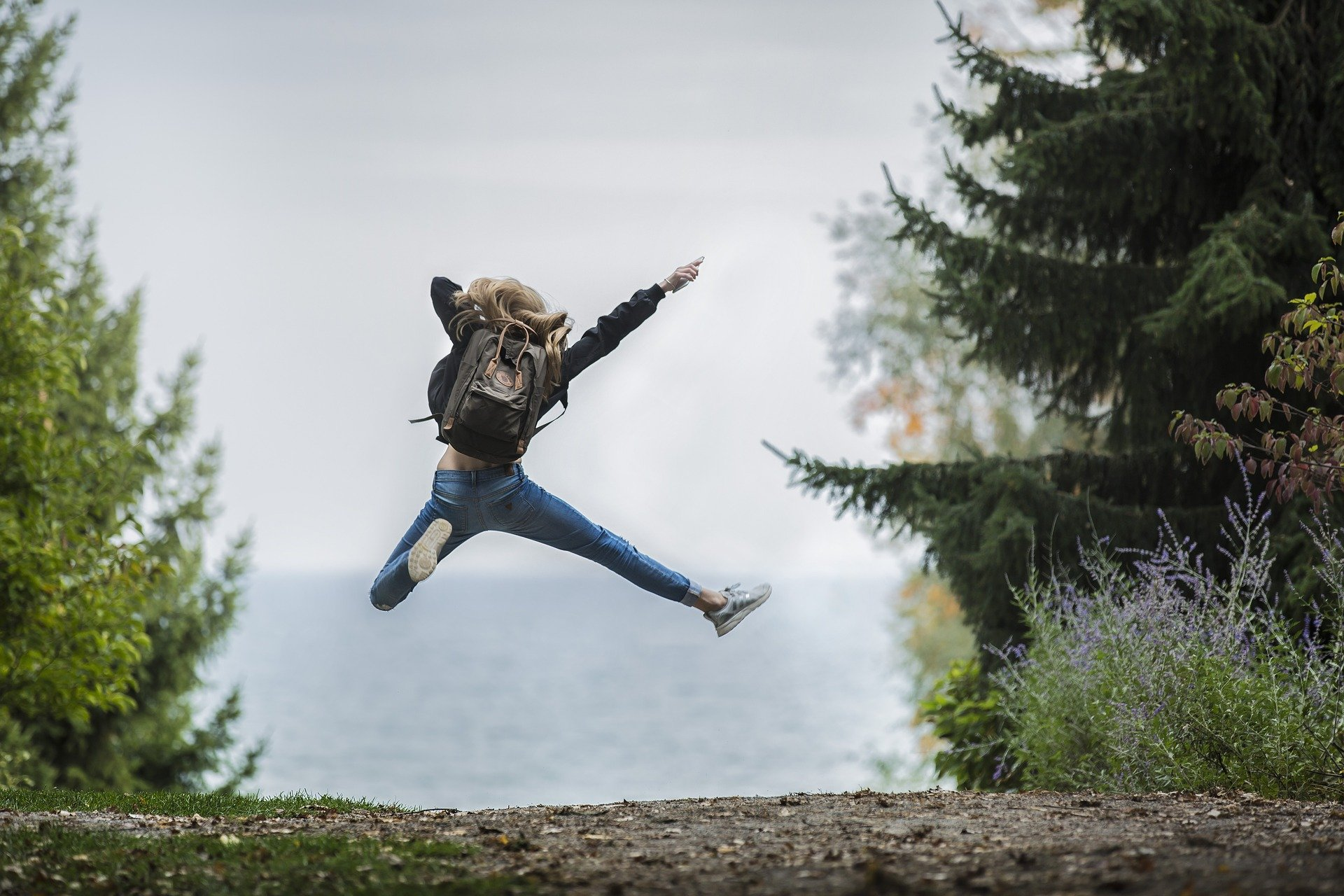 Girl wearing a backpack and jumping in the air.