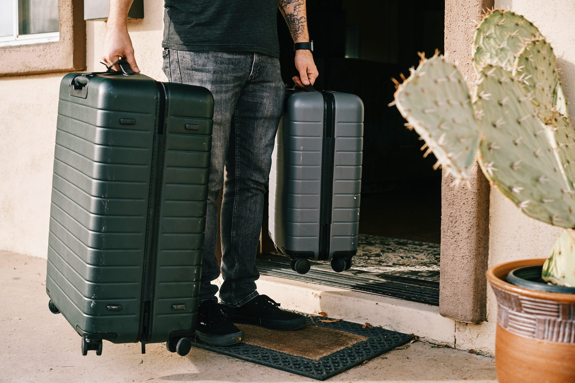Man holding two suitcases at the entrance of a door.
